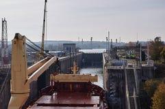 Embarcação do navio mercante com os dois guindastes que passam fechamentos nos grandes lagos, Canadá no tempo de inverno Imagens de Stock Royalty Free