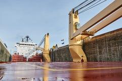Embarcação do navio mercante com os dois guindastes que passam fechamentos nos grandes lagos, Canadá no tempo de inverno Fotos de Stock