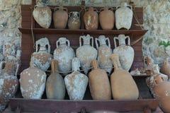 Embarcações e jarros antigos nas prateleiras no jogo Foto de Stock