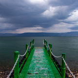 Embarcadero abandonado en las nubes amenazadoras oscuras de la salida del sol Foto de archivo libre de regalías