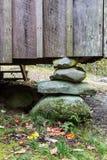 Embarcadero apilado de la fundación de la roca debajo de la pared del tablero y del listón en un hogar apalache rústico Imagen de archivo