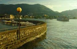 Embarcadero con el barco en un lago Como de la montaña en la puesta del sol fotos de archivo libres de regalías