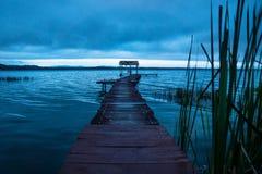 Embarcadero con la choza detrás de la hierba móvil a lo largo de la orilla del lago antes de la puesta del sol, EL Remate, Peten, fotografía de archivo libre de regalías