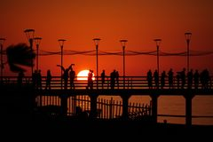 Embarcadero con la gente que se relaja por la puesta del sol Foto de archivo libre de regalías