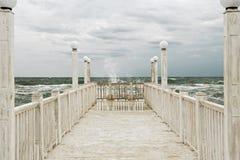 Embarcadero con las barandillas de madera blancas en el mar durante una tormenta imagenes de archivo