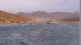 Embarcadero con las naves y los yates en el fondo de monta?as en el desierto de Egipto almacen de video