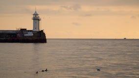 Embarcadero con un faro en la puesta del sol metrajes