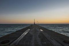 Embarcadero concreto marino con la grúa en la puesta del sol Fotos de archivo