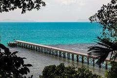 Embarcadero concreto rodeado por el bosque tropical con el océano azul Foto de archivo