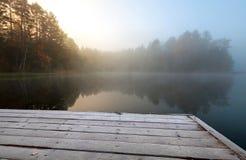 Embarcadero congelado en el lago por todavía del frío mañana brumosa Fotos de archivo