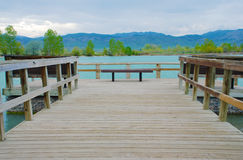 Embarcadero de invitación del lago con la vista de montañas púrpuras imagen de archivo