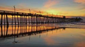 Embarcadero de la playa en la puesta del sol foto de archivo