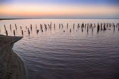 Embarcadero de madera arruinado en el lago en la salida del sol Imagenes de archivo