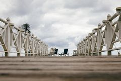 Embarcadero de madera con dos sillas Foto de archivo libre de regalías