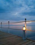 Embarcadero de madera con la lámpara en la puesta del sol Imagen de archivo