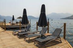 Embarcadero de madera con los sunbeds y los parasoles Imágenes de archivo libres de regalías