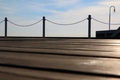 Embarcadero de madera con una linterna en un fondo del cielo claro Fotografía de archivo libre de regalías