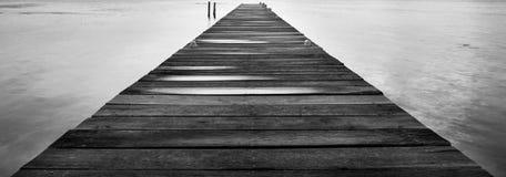 Embarcadero de madera en Dawn Black y el blanco foto de archivo