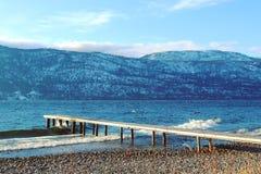 Embarcadero de madera en el lago en la estación del invierno Foto de archivo