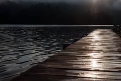 Embarcadero de madera en el lago en la madrugada Imágenes de archivo libres de regalías