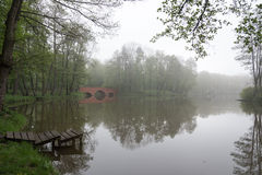 Embarcadero de madera en el pequeño lago en un parque por mañana brumosa Foto de archivo