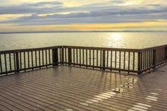 Embarcadero de madera en la playa en la puesta del sol Foto de archivo