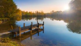 Embarcadero de madera en un lago encalmado en la puesta del sol Imágenes de archivo libres de regalías