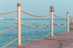 Embarcadero de madera de la playa con los postes y las cuerdas imágenes de archivo libres de regalías