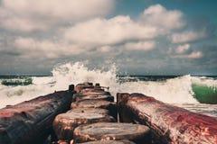 Embarcadero de madera que estira en el mar Báltico tempestuoso, escupitajo de Curonian foto de archivo