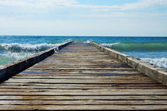 Embarcadero de madera que lleva en el mar azul Imagen de archivo libre de regalías