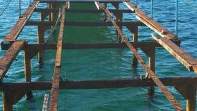 Embarcadero de madera viejo destruido en el mar Marco de acero oxidado, reparación almacen de metraje de vídeo