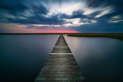 Embarcadero de madera viejo en el lago tranquilo en la puesta del sol Foto de archivo