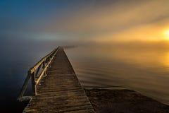 Embarcadero de madera viejo que alcanza en el lago de niebla en crepúsculo de la mañana imágenes de archivo libres de regalías