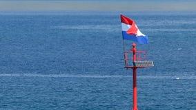 Embarcadero de piedra con la bandera del faro y del vuelo en la luz del día, constante metrajes