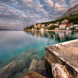 Embarcadero de piedra en pequeño pueblo cerca de Omis en el amanecer, Dalmacia Foto de archivo