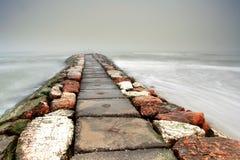 Embarcadero de piedra rojo y blanco en la niebla Imagenes de archivo
