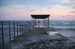 Embarcadero del mar por la tarde y una mujer en una soledad foto de archivo