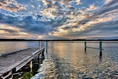 Embarcadero del río en la puesta del sol, con el cloudscape dramático Fotografía de archivo libre de regalías