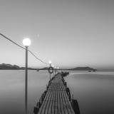 Embarcadero en el mar en el amanecer. Blanco y negro Fotos de archivo libres de regalías
