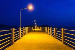 Embarcadero en la noche con las luces ámbar en un fondo del cielo azul Imagenes de archivo