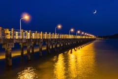 Embarcadero en la noche con las luces ámbar en un fondo del cielo azul Imagen de archivo libre de regalías