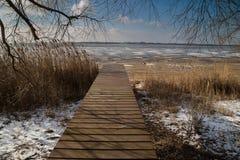 Embarcadero en la orilla de un lago congelado Foto de archivo