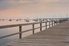 Embarcadero en la puesta del sol con los veleros en el fondo Imagenes de archivo