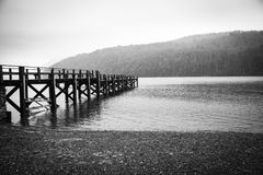Embarcadero en un lago brumoso Foto de archivo