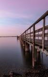 Embarcadero en un lago en la puesta del sol Fotografía de archivo