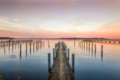 Embarcadero en un lago en la puesta del sol Imagenes de archivo