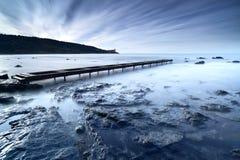 Embarcadero o embarcadero de madera en un océano azul por la mañana Exposu largo Fotos de archivo libres de regalías