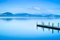 Embarcadero o embarcadero de madera y en un reflectio azul de la puesta del sol y del cielo del lago Imagen de archivo libre de regalías