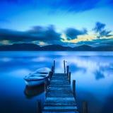 Embarcadero o embarcadero de madera y un barco en una puesta del sol del lago Versilia Tusca Foto de archivo libre de regalías