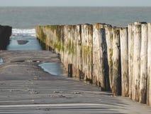 Embarcadero que entra el agua guardar la arena en la playa fotos de archivo